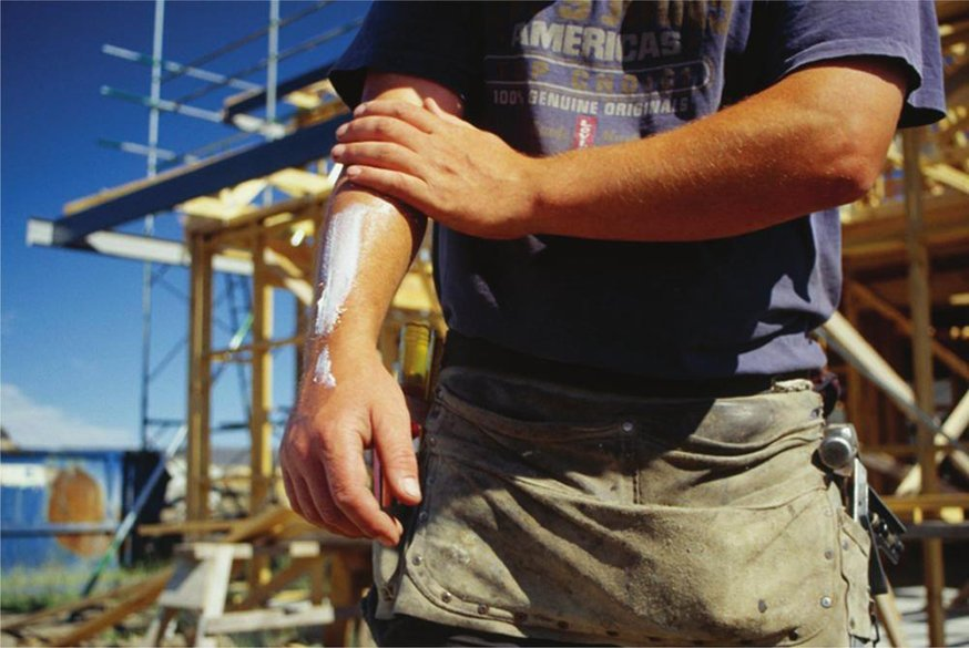 Guide to ensuring worker safety outdoors - builder applying sun cream